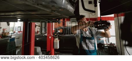 Young Caucasian Mechanic Checking Car Brakes While Standing Under Bottom Of Lifted Auto On Car Servi