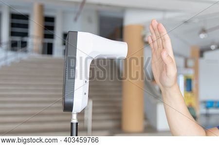Young man used his palm to touch the sensor of the thermometer temperature using a non-contact infra