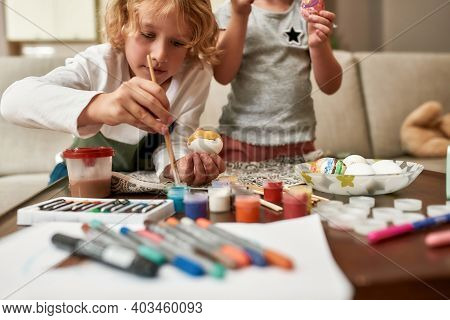Close Up Of Cute Little Boy Painting Colorful Easter Eggs Together Wih His Sibling Sister While Spen