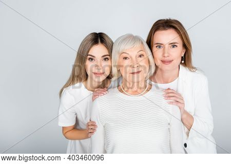 Three Generation Of Women Smiling While Looking At Camera Isolated On Grey