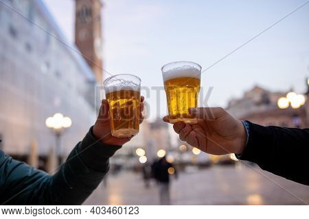 Closeup Of Two Hands Clinking Beer Stein Glasses. Toasting With A Pint Of Draft Beers On The City Sq