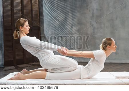Young Woman Is Getting Thai Massage Treatment By Therapist. Traditional Asian Stretching Therapy.