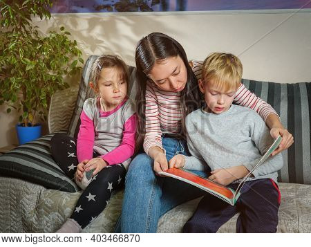 Girl Nanny Reads A Book To Children. Working With Children At Home. Education And Pastime With Child