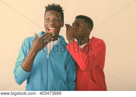 Studio Shot Of Young Black African Man Whispering To Happy Slim Black African Man Smiling While Thin