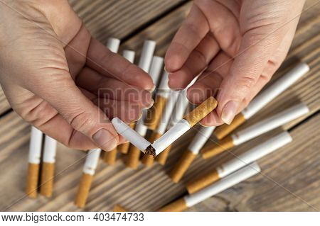 Stop Smoking Cigarettes Concept. Portrait Of Beautiful Smiling Girl Holding Broken Cigarette In Hand