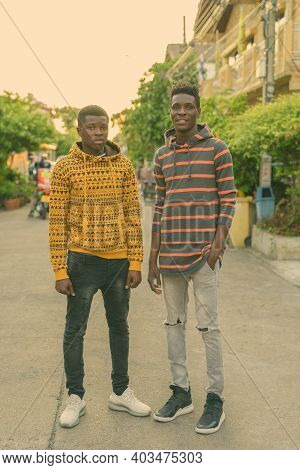 Full Body Shot Of Two Young Happy Black African Friends Smiling While Standing Outdoors
