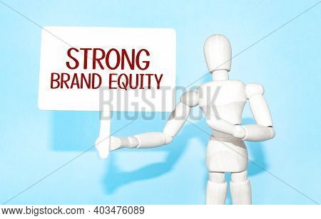 The Wooden Man Holds A White Sign With The Text Strong Brand Equity In His Hands. The Content Of The