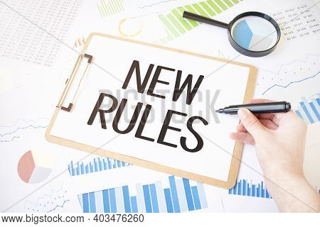 Text New Rules On White Paper Sheet And Marker On Businessman Hand On The Diagram. Business Concept