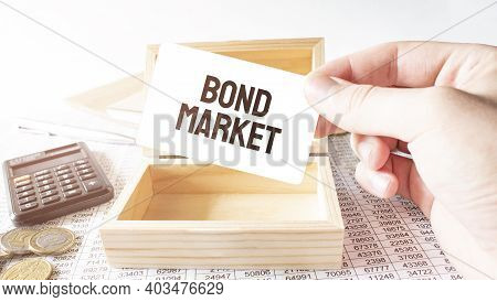 Businessman Hold White Card With Text Bond Market Calculator,wood Box,money And Financial Documents