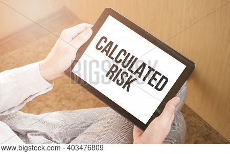 Man Using Digital Tablet, Close-up, Coffee And Keyboard On The Background. Text Calculated Risk
