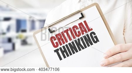 Text Critical Thinking On White Paper Plate In Businessman Hands In Office. Business Concept