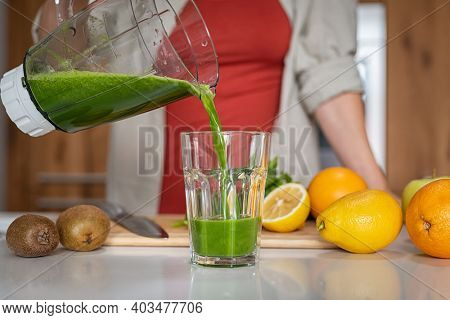 Close up of young healthy woman pouring fresh juice in glass. Girl pouring a green detox smoothie from blender to a tumbler at home. Woman prepare freshly made antioxidant smoothie from grinder jar.