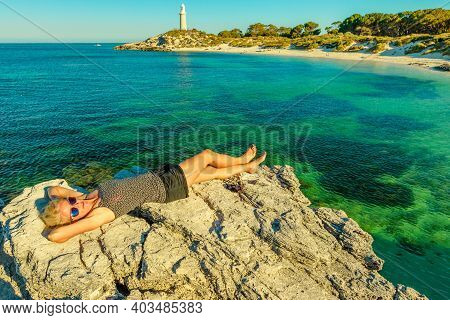 Caucasian Tourist Girl Sunbathes On Rocks Looking Turquoise Waters Of Pinky Beach. The Historic Bath