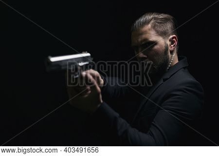 Real Bandit In Black Suit Aiming With Gun Over Black Studio Background. Concept Of Danger And Mafia.