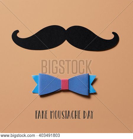 closeup of a moustache, made with a cutout of a black cardboard, a bow tie and the text fake moustache day on a brown background, in square format