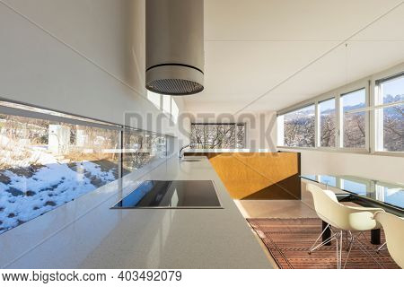 Kitchen with dining room of a cozy and modern apartment. large window with a view on a blue sky mountains to forest.
