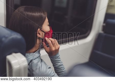 Mandatory face covering in public transport during coronavirus pandemic. Woman commuter putting on cloth mask. Passenger touching mouth cover on commute.