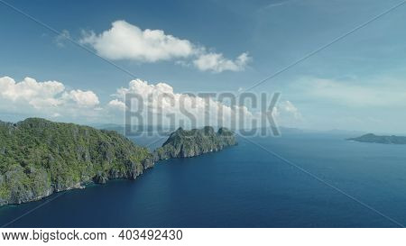 Hilly islands at blue ocean coast aerial view. Nobody nature scenery of Palawan, El Nido Isles, Philippines. Green tropic forest at mount ranges under fluffy clouds on sky. Cinematic drone shot
