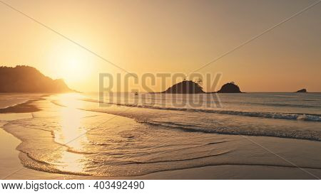 Sunset at sea bay waves aerial. Sun silhouette of rock islands at ocean gulf. Picturesque seascape of Philippines, Asia. Sunshine reflect over paradise sand beach. Cinematic soft light drone shot