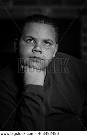 Handsome african American boy resting head on fist