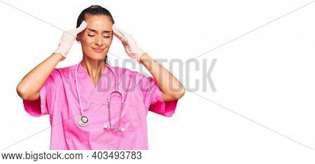 Young hispanic woman wearing doctor uniform and stethoscope suffering from headache desperate and stressed because pain and migraine. hands on head.
