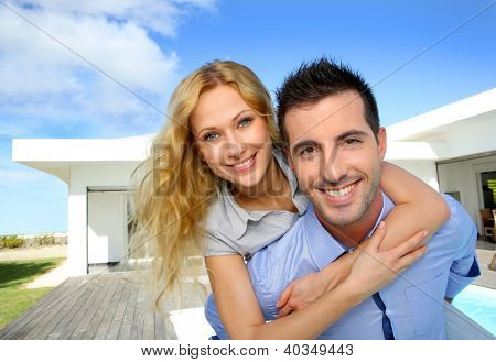 Happy new property owners in front of their house