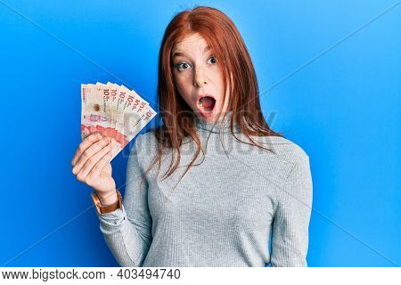 Young red head girl holding 10 colombian pesos banknotes scared and amazed with open mouth for surprise, disbelief face
