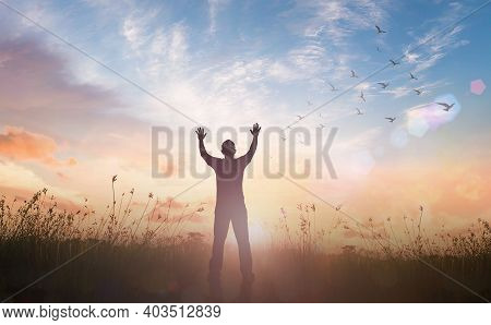 Praise And Worship God Concept: Silhouette Of Healthy Man Raised Hands At Meadow Sunset Background