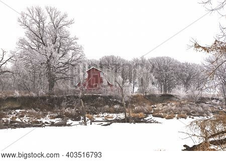 An Old Red Hip Roofed Barn Is Surrounded By Trees Covered With Hoar Frost