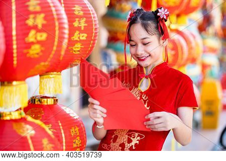 Asian Girl Wearing Red Traditional Chinese Cheongsam Decoration Holding Red Envelopes In Hand And La