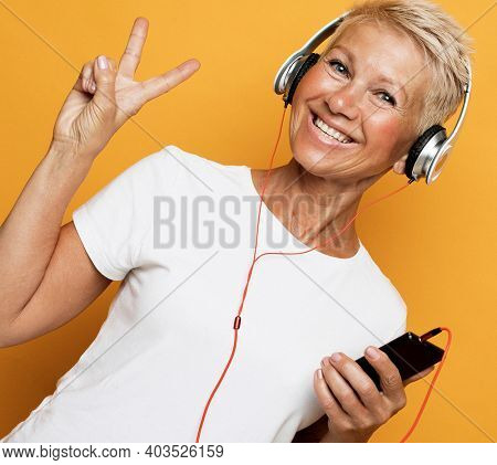 Middle age beautiful blond woman listening to music using headphones over yellow background show victory sign over yellow background