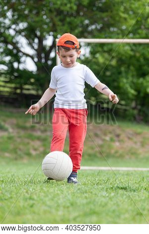 Little Boy Kicking Ball In The Park. Playing Soccer (football) In The Park. Sports For Exercise And