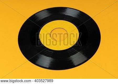 Old Vinyl Disc On Yellow Background. Old Vintage Vinyl Record.