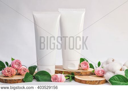 White Unbranded Tubes For Cosmetics With Wood Cuts, Small Pink Roses And Cotton Flowers On White Bac