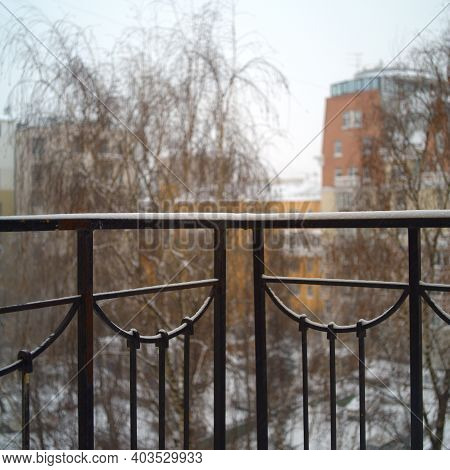 Snow On A Balcony Handrails, An Urban Landscape In The Blurred Background