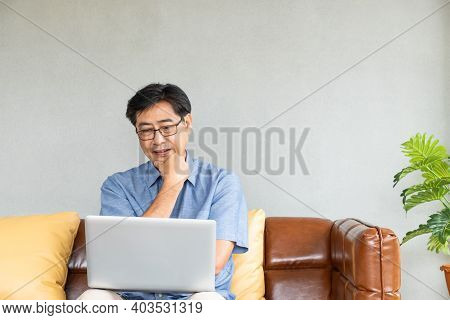 Selective Focus At Old Asian Men Sit On The Couch, Having Difficulty And  Problem With Internet And