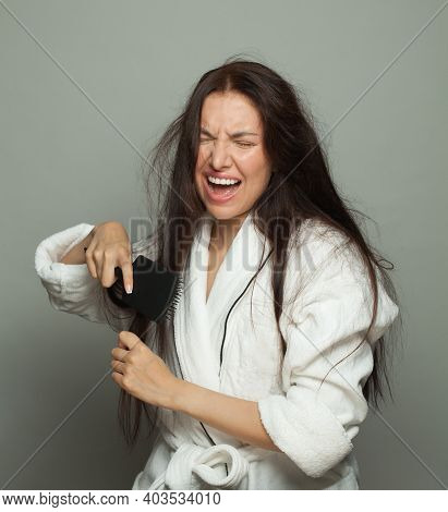 Disgruntled Woman Combing Her Tangled Hair On White Background, Hair Care And Hair Problem Concept