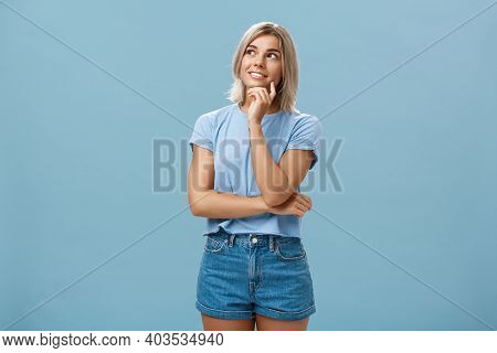 Dreamy Thoughtful And Creative Artistic Blonde Woman In Denim Shorts And T-shirt Smiling Curiously T