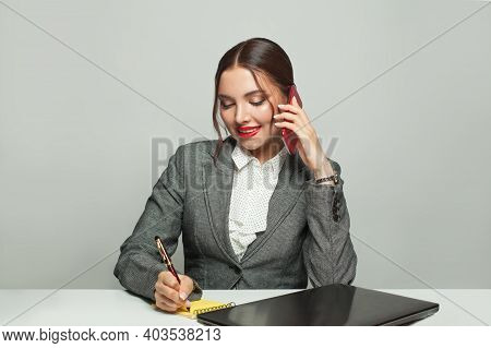 Businesswoman With Laptop And Phone Sitting In Office