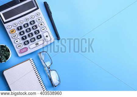 Calculator Keypad On A Blue Background.notebook, Pen, Glasses, Desktop. Finances Top View. Copy Spac