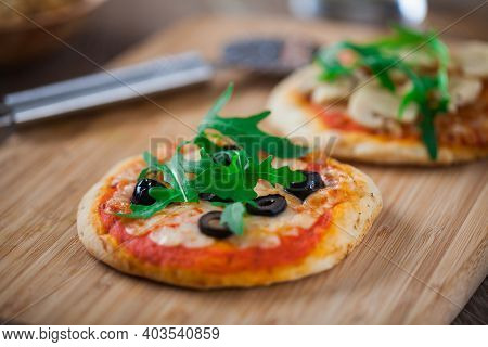 Mini Pizzas Served On Wooden Board. High Quality Photo.