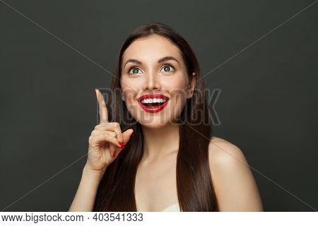 Happy Adorable Woman With Long Healthy Straight Hair Pointing Up. Skincare And Facial Treatment Conc