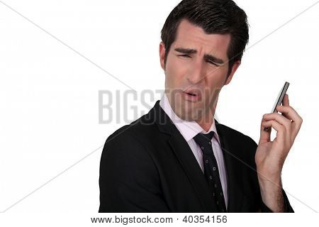 Businessman grimacing at his phone