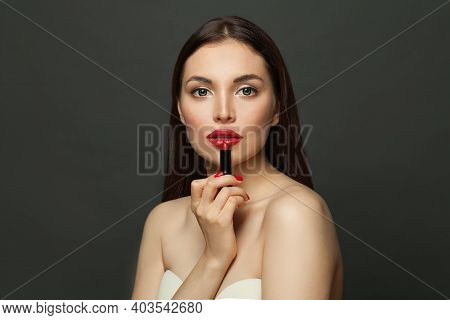 Beautiful Young Woman Holding Red Lipstick Near Lips On Black Background