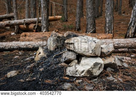 The Remains Of A Fire In The Forest. A Pile Of Rocks And Ashes From Burning Trees. Traces Of Tourist