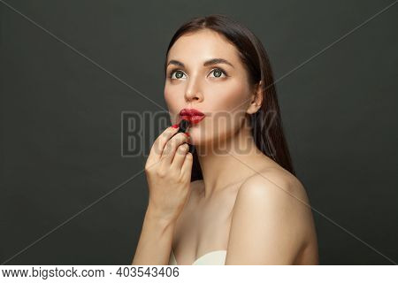 Young Woman Applying Red Lipstick Makeup On Lips On Black Background