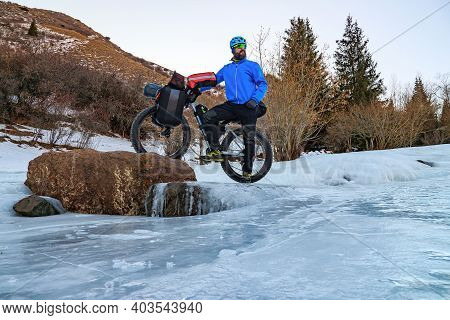 Bearded Male Traveler Cyclist In Winter In The Mountains On A Frozen River Among The Ice. Winter Tra