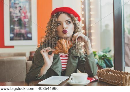 Cute Young Woman Drinking Coffee And Eating French Croissant In Cafe