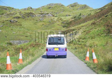 Purple Campervan In Remote Mountain Road Trip