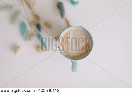 Cup Of Coffee And Dried Flowers At White Background. Green Mug With Hot Foamy Cappuccino Top View